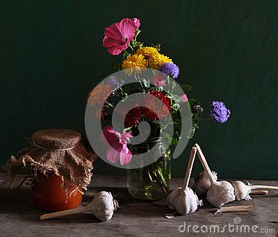 Still life with different flowers and jar of jam