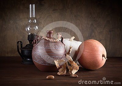 Still-life with a jug an oil lamp and pumpkins