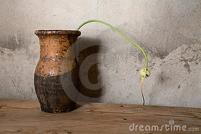 Still-life with an old jug against  wall