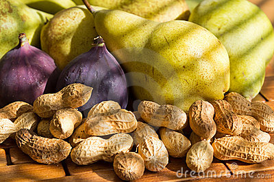 Still life of peanuts, red figs, green pears