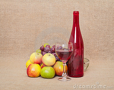 Still-life - red bottle and fruit against a canvas