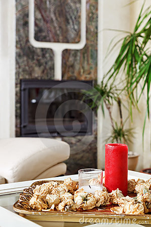 Still life with red candle and dried rose flowers