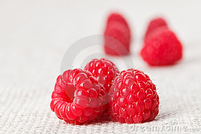 Still life with three red raspberry on gray linen