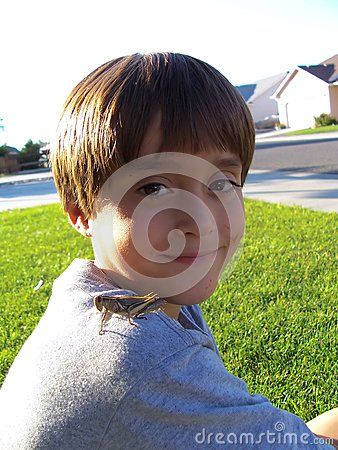 Stock Photo of Boy Playing with Grasshopper