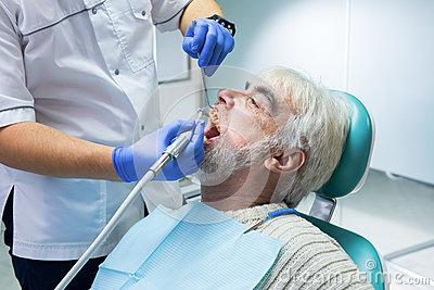 Stomatologist is cleaning teeth. Stock Photo