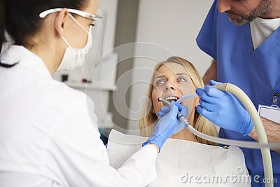 Stomatologist and her assistant treating woman for dental cavity Stock Photo