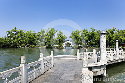 Stone arch and zigzag bridge in lake