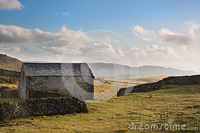 Stone barn and rock walls in Autumn sunset landscape