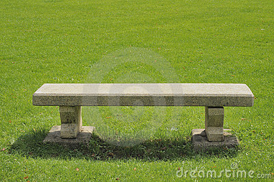 Stone bench on green field
