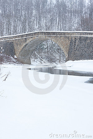 Stone Bridge over Stream in Winter