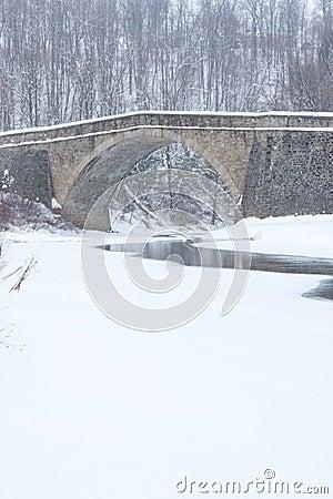 Stone Bridge over Stream in Winter