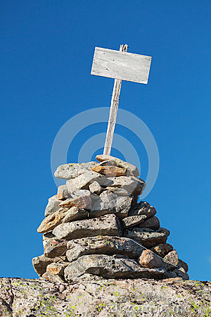 Stone cairn with empty white wooden label