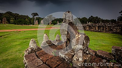 Stone carving of Angkor ruin with stormy sky