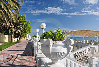 Stone flower urns and palm trees at seafront