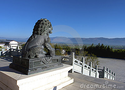 Stone lion statue overlooking city