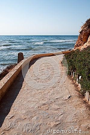 Stone pavement path along rocky seashore.