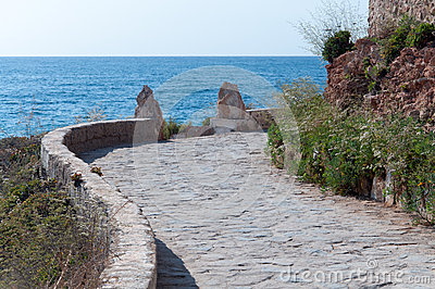 Stone pavement path along rocky seashore.