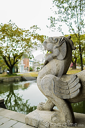 Stone sculpture of myth by pond,China
