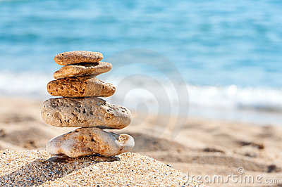 Stone tower in sand against sea.