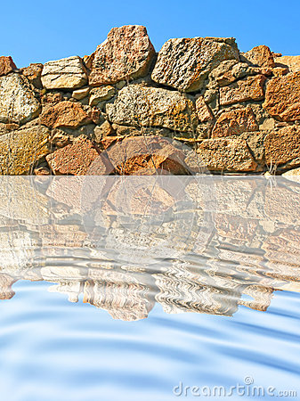 Stone wall being reflected in ripple blue water.