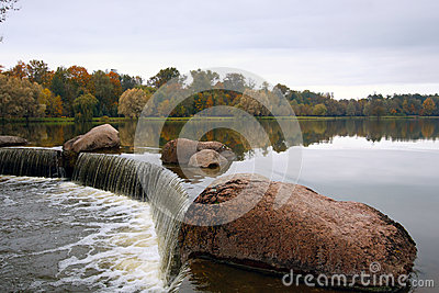 Stone and waterfall against overcast sky