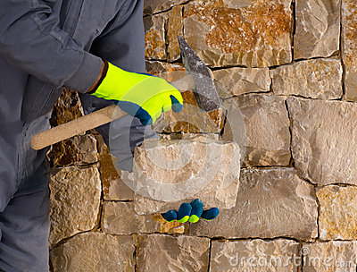 Stonecutter mason with hammer and stone working masonry