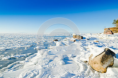 Stones in ice on the Baltic Sea coast
