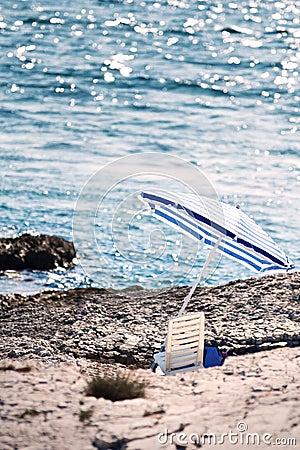 The stony beach with parasol