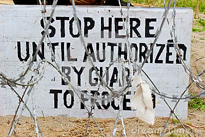 Stop here - military board in barbed wire
