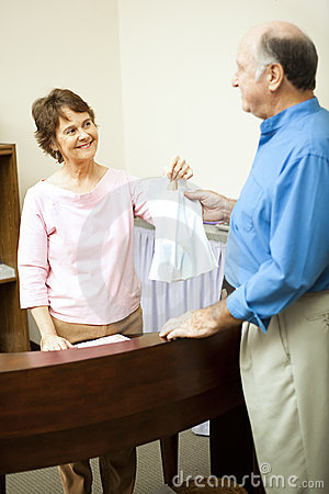 Store Clerk Handing Bag