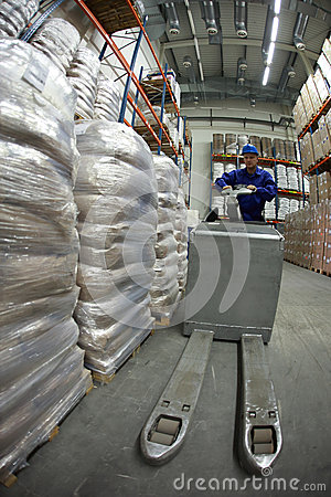 Storehouse worker at work with forklift