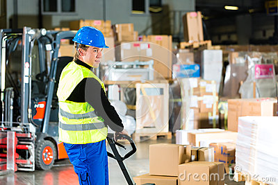 Storeman with mover at warehouse of forwarding