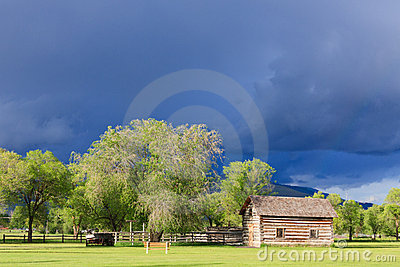 Storm clouds over log cabin.