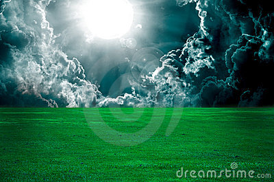 Storm clouds over meadow with green grass