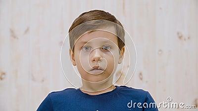 Strålningskänslig med skrämmande blickar mot kameran i ljusstudio Stäng den rädda pojkens ansikte Överspänd tonåring på ljus arkivfilmer