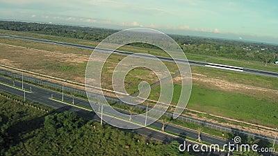Strada per il campo vicino all'aeroporto Pista vicino alla città Un drone che vola lungo un'autostrada vuota archivi video