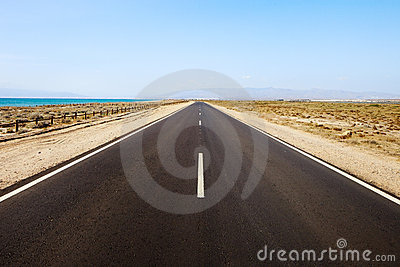Straight road in desertic seascape. Andalusia.