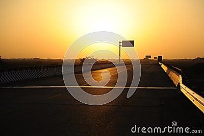 Straight  road in the gobi at sunrise