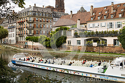 Strasbourg s cityscape with the Ill river and a touristic boat Editorial Stock Image