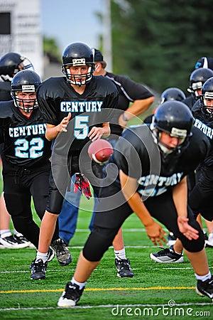 Strateeg van de Voetbal van de jeugd ontvangt de Amerikaanse bal Redactionele Stock Foto