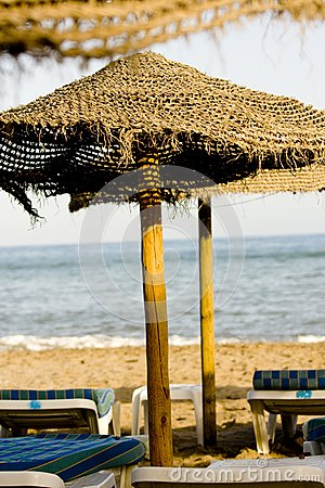 Straw umbrella and chairs