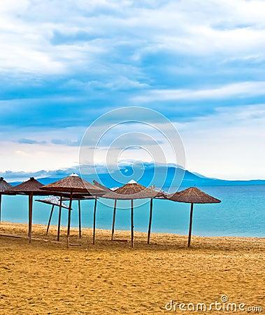 A straw umbrella on a tropical beach with sky