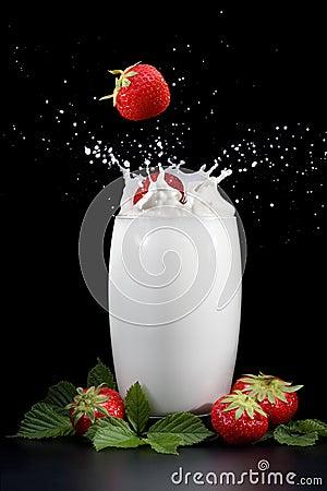 Strawberries splashing into milk