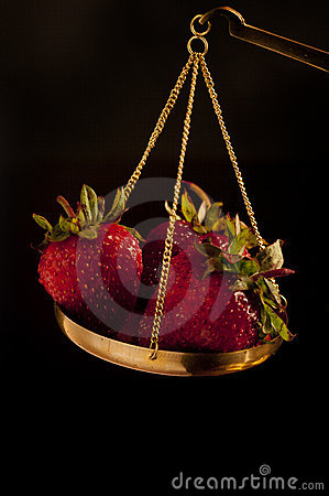 Strawberry on balance scale
