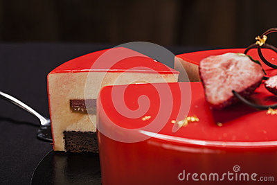 Strawberry cake covered with red mirror glaze decorated with berry pieces, gold and chocolate. A modern cake with a cut piece clos Stock Photo