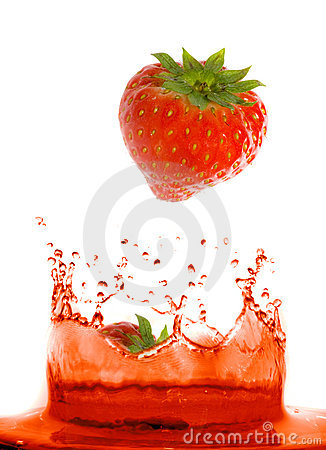Strawberry falling in juice.