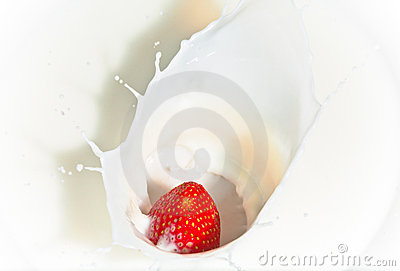 The strawberry falling in milk