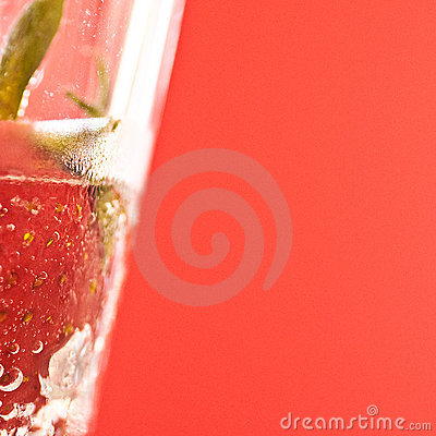 Strawberry immersed in fizzy water in a glass