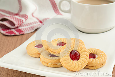 Strawberry jam sandwich biscuits with coffee cup
