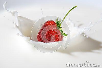 Strawberry splashing into milk